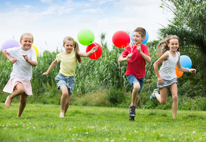 Four friendly kids running on green lawn